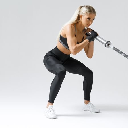 Close-up photo of hamstring, quad and booty workout Attractive fitness model workout with barbell row Sporty woman on white background