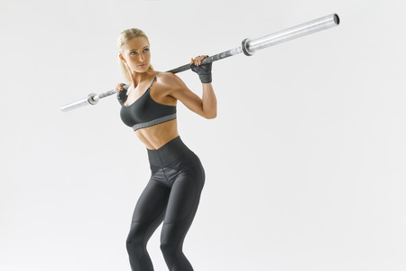 Photo of beautiful strong young woman with barbell and weight plates Fit young female athlete lifting heavy weights Caucasian female model performing barbell back squat Foto de archivo