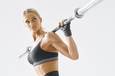Strong young woman exercising with weights against white background. Shot of caucasian woman with muscular build working out holding barbell and looking confident Imagens