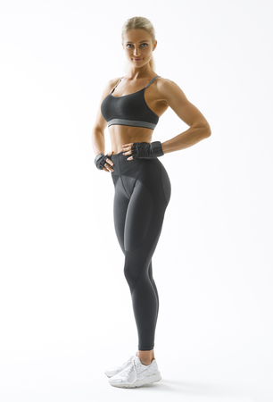 Full length portrait of fitness woman standing with her arms on hips Female model in sportswear over white background Mockup