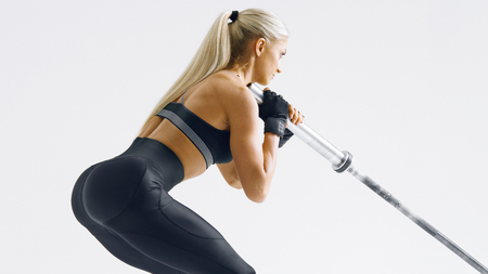 Cropped photo of confident young woman exercising with barbell at fitness gym Female bodybuilder turned back working out with heavy weights at training gym