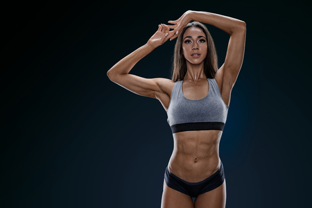 Confident athletic woman with sixpack abs on black background Young female bodybuilder with strong abdominal muscles posing with her hands joined overhead, with copy space and clipping path Mockup