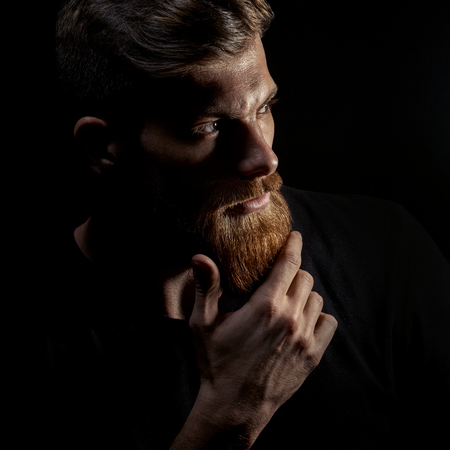 Portrait of young bearded man isolated at black background Guy with beard thoughtful, pensive, charming, looking forward Trendy hipster think of problem solving, finding solution