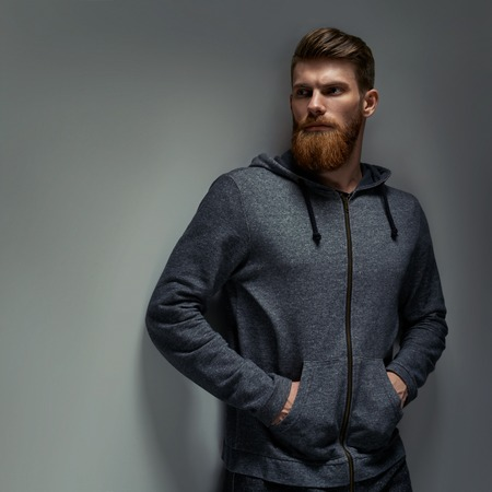 Image of single standing in profile young handsome serious bearded man in grey hoodie over grey background with copy space. Foto de archivo - 100188253
