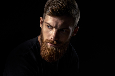 Close-up image of serious brutal bearded man on dark background Confident and dramatic concept Foto de archivo - 100188256