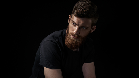 Studio portrait of fashionable bearded man looking forward posing against black wall. Emotions and feelings. Young hipster with beard and fair skin Foto de archivo - 100188257