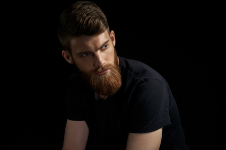 Portrait of handsome single bearded young man with serious expression and black shirt looking over black background with copy space Foto de archivo - 100188258