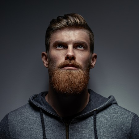 Portrait of serious young bearded man weared gray hoodie looking up Studio shot over black background. Foto de archivo - 100188259