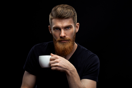 Beautiful young bearded man drinking coffee and looking at camera Resting handsome perfect hairstyle man drinking espresso coffee holding cup of coffee in hand Studio shot on black background. Foto de archivo - 100188260