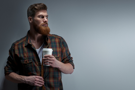 Dramatic light studio shot of young caucasian bearded stylish man with cup of coffee Handsome hairstyling male portrait holding coffee to go cup over black background Free copy space template. Foto de archivo - 100188261