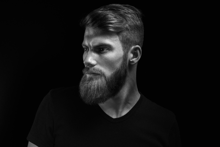 Black and white studio shot of confidence attractive hipster Dramatic light concept Black background Copy space Bearded man Foto de archivo - 100188266