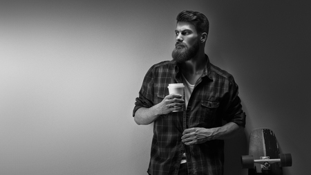 Black and white photo of bearded stylish businessman with coffee in hand Handsome confident perfect hairstyle man having coffee indoor Male  taking rest and drinking fresh morning coffee to go. Foto de archivo - 100188268