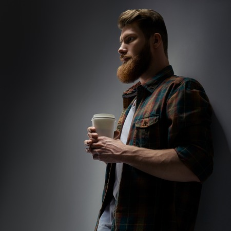 Close up side view dramatic shot of handsome young bearded man having coffee indoors Male taking rest and drinking fresh morning coffee to go Side view shot of young businessman with coffee in hand. Foto de archivo - 100400729