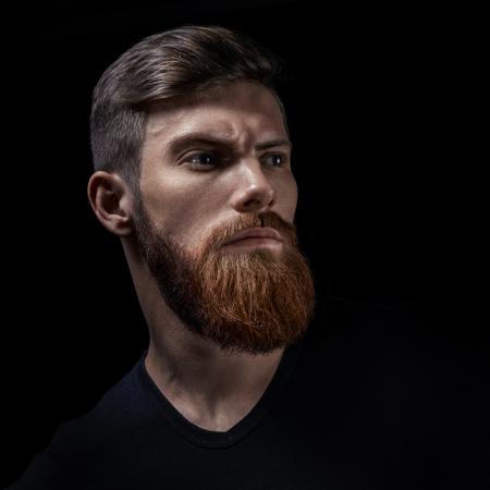 Studio portrait of stylish bearded caucasian man in a black shirt over black background. Foto de archivo - 100460358