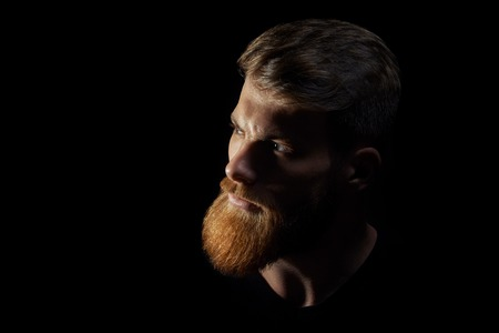 Close up single serious handsome caucasian young man with ginger hair and well groomed beard over black background
