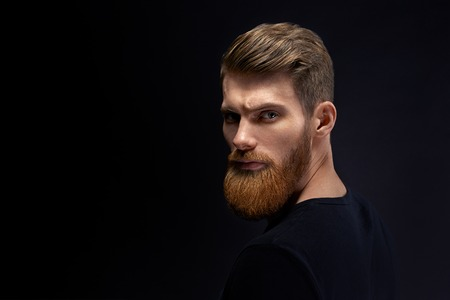Fashion male model with stylish hair and beard. Young man with long beard and mustache on serious face. Barber fashion and beauty. Foto de archivo - 124440982