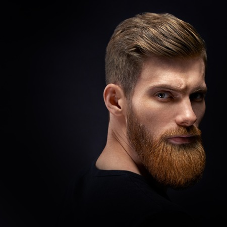 Fashion model with stylish hair and beard. Barber fashion and beauty. Portrait of handsome single bearded young man with serious expression Foto de archivo - 124440983