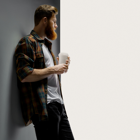 Portrait of handsome single bearded young man with serious expression having coffee indoors and white short t-shirt looking over white background with free copy space Foto de archivo - 124440985