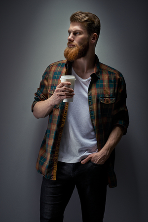 Dramatic light concept photo of confident young bearded man holding cup of coffee Side view portrait of male model with ginger hair Foto de archivo - 124441010