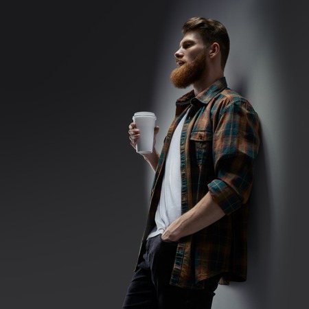 Dramatic shot of handsome young bearded man having coffee Male taking rest and drinking fresh morning coffee to go Side view shot of young bearded man with coffee in hand Template mockup copy space. Foto de archivo - 124441011