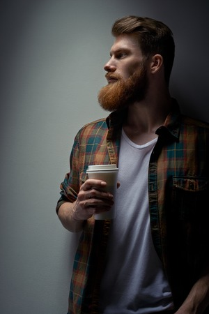 Close up side view shot of young bearded stylish businessman with coffee in hand Handsome confident perfect hairstyle man having coffee indoor Male taking rest drinking fresh morning coffee to go. Foto de archivo - 124441012