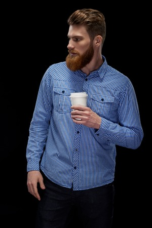 Close up side view shot of handsome young bearded man having coffee indoors Male taking rest and drinking fresh morning coffee to go. Young businessman with coffee in hand. Foto de archivo - 124441015