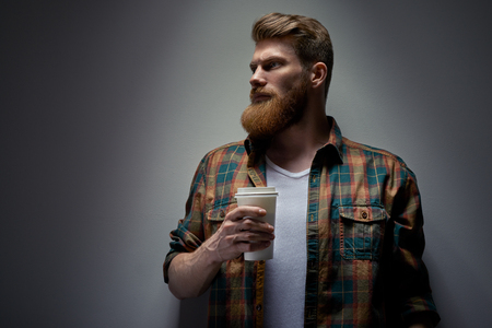 Close up shot of side view of young bearded man drinking cappuccino coffee Coffee on the go studio shot on gray background Free space for brand corporate, mockup template Foto de archivo - 124441014
