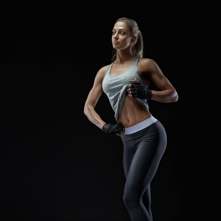 Young sports model in sportswear shows abs Fitness woman in sports clothing, gloves. Athletic young woman showing her well trained body, six pack, perfect abs, shoulders, biceps, triceps and chest.