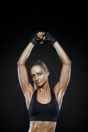Fit attractive woman in sportswear standing with her hands rise up. Cropped shot of female sports model standing against black background. Beautiful fitness, great design for any purposes.