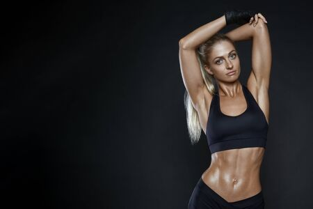 Sexy shapely well trained young woman with a healthy body posing in black sportswear with her arms raised over black with copy space. Sports training. Healthy lifestyle young caucasian model. Banco de Imagens