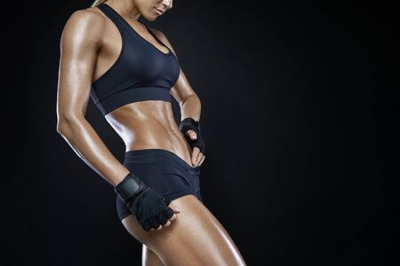 Athletic woman with strong abdominal muscles posing with her hands on her hips with copy space. Attractive muscular woman with gloved hands on strong abs. Muscular pumped woman after workout. Stock Photo