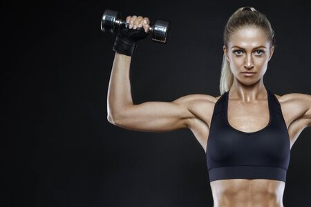 Fit strong young woman lifting weights working out with dumbbells confidently looking to the camera flexing her arm on black with copy space. Fitness exercising. Energy fitness motivation. Stock Photo