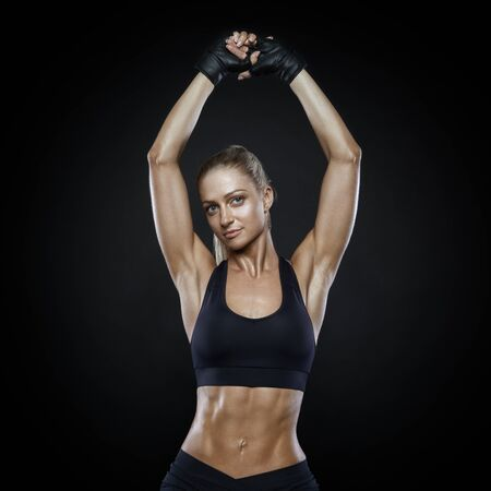 Image of fitness woman in sports clothing, gloves. Fitness athletic young woman showing her well trained body, six pack, perfect abs, shoulders, biceps, triceps and chest. Energy fitness motivation.