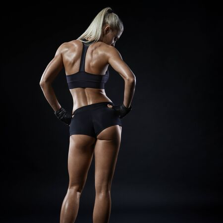 Fitness athletic young woman showing her well trained body, turned back. Image of sporty woman in sports clothing looking down relaxing. Energy fitness motivation concept.
