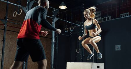 Close up shot of young fitness woman is doing exercises with the help of a personal trainer in a modern gym Trainer helping woman on her work out routines. Sporty girl doing a box jump at the gym.
