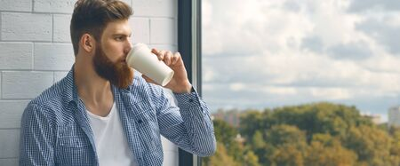 Close up portrait of a bearded young man drinking takeaway coffee. A bearded man with a mustache looks out the large window.