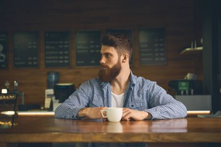 Bearded man drink morning coffee indoor. Hipster hold portable drink in morning. Breakfast drink. His morning cup of good mood Lifestyle concept