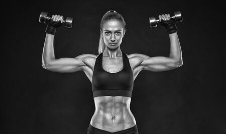 Black and white shot of young female bodybuilder working out with hand weights and shorts curling dumbbell over black background Caucasian woman with muscular body, abs Mockup.