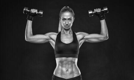Colpo in bianco e nero di giovane bodybuilder femminile che lavora con pesi a mano e pantaloncini curling manubri su sfondo nero Caucasica donna con corpo muscoloso, abs Mockup.
