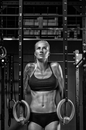 Atleta caucásico de crossfit femenino en ropa deportiva negra que ejercita en anillos de gimnasia en el gimnasio Ejercicio de mujer sosteniendo anillos de gimnasta y mirando hacia arriba. Entrenamiento en el gimnasio. Fotografía en blanco y negro.