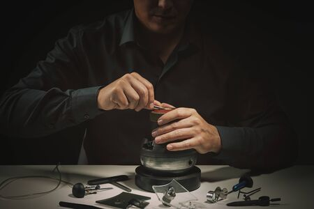 Engraver jeweller craftsman closeup. Focus on hands. Professional tools for jewelleries craftmanship.