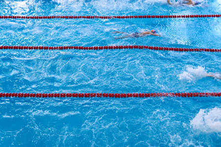 Lagging behind. Swimmers in motion slightly blurred. Children swim in the pool. Swimmers competition. Unidentified young swimmers. The concept of a healthy lifestyle among the young generation