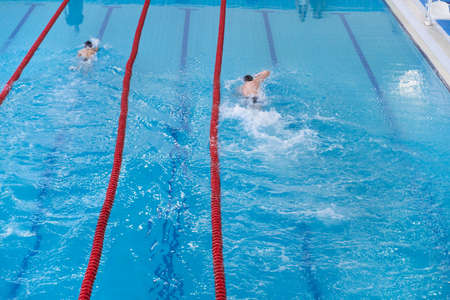 Children swim in the pool. Unidentified young two swimmers. Top view shot. The concept of a healthy lifestyle. Child practice water sport. Swimmers in motion slightly blurred