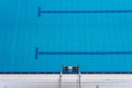 Swimming pool edge with a steel ladder Top view Empty sports swimming pool Horizontal orientation