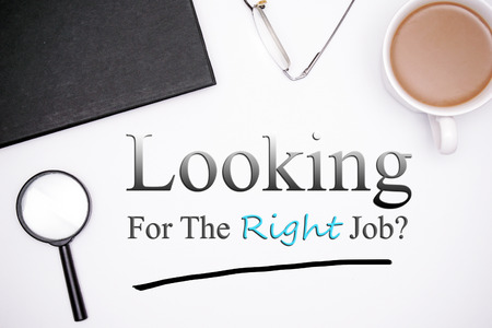 looking for job: flatlay of office equipments. a cup of coffee, pair of glasses, black book, and a magnifying glass. looking for the right job text Stock Photo