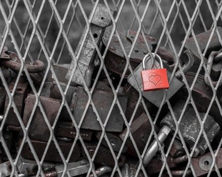 tradition: A red heart shaped lock connected to the cage with old rusty