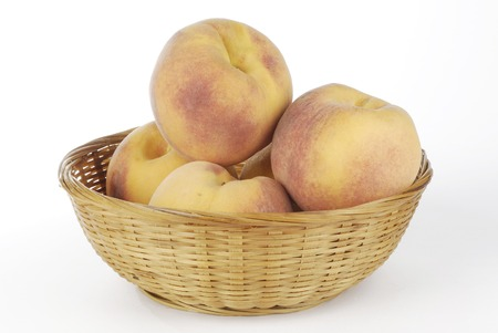 willow fruit basket: a wicker basket full of peaches Stock Photo