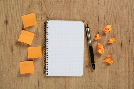 Paper notes and notebook on brown background