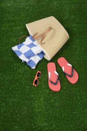 flip flops: Bag, towel and flip flops in the grass