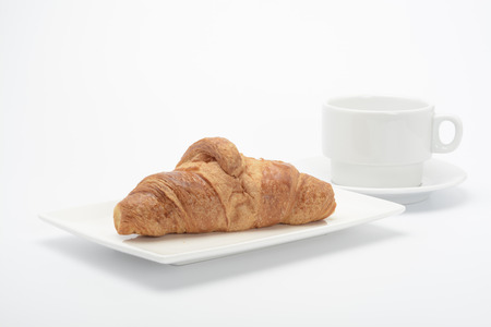 calory: One croissant on a plate on white background
